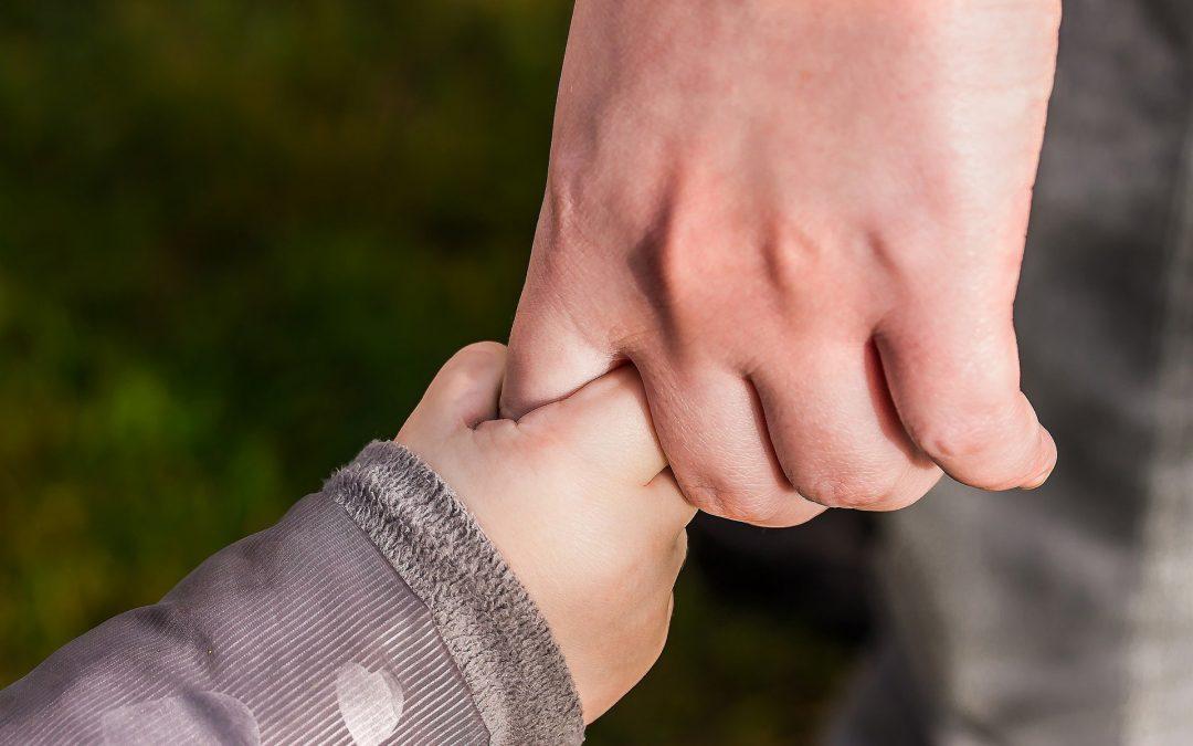 Adulto da la mano a un niño