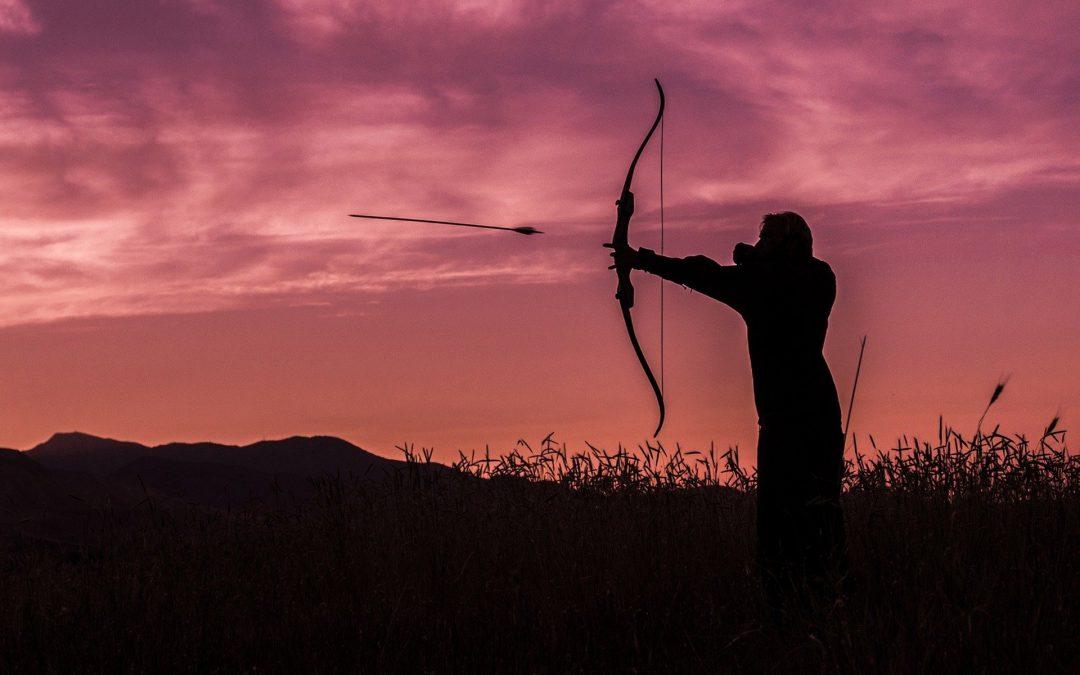 Persona con arco y flecha apuntando al objetivo
